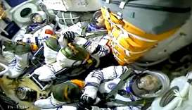 Chinese astronauts Nie Haisheng, Liu Boming, and Tang Hongbo are seen in a capsule as China launches