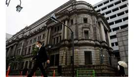 A man wearing a protective mask walks past the headquarters of the Bank of Japan in Tokyo, May 22, 2