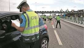 Police officers stop cars at a checkpoint in Lisbon.