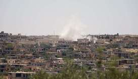 Smoke billows following reported bombardment by government forces in the Syrian northwestern town of