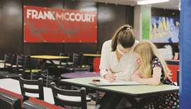 A mother and her daughter fill a ballot at a cafeteria's table in a polling station at the Frank McC