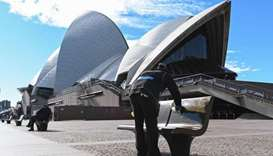 A worker cleans public seating outside Opera House in Sydney, after authorities locked down several