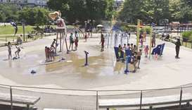 Children cool off at a community water park on a scorching hot day in Richmond, British Columbia.