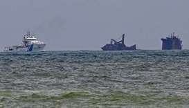 An Indian Coast Guard ship (L) approaches near the Singapore-registered container ship MV X-Press Pe