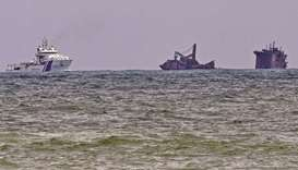 An Indian Coast Guard ship (left) approaches near the Singapore-registered container ship MV X-Press