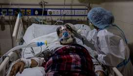 A medical worker tends to a patient suffering from the coronavirus disease, inside the ICU ward at H