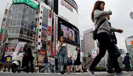 People cross a street in the Shinjuku shopping and business district in Tokyo, Japan