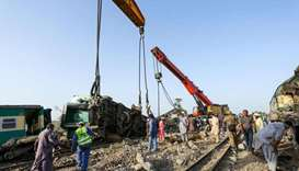 Railway labourers work to clean the wreckage from a railroad track in Daharki, a day after a packed