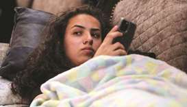 Jana Kiswani, 16, looks on as she rests at home after she was injured when a police officer shot her