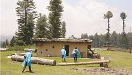 Healthcare workers head to a hut to inoculate shepherds during a Covid vaccination drive at a forest
