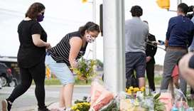 People pay their respects at the scene where a man driving a pickup truck struck and killed four mem