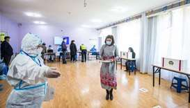 An election worker wearing a protective suit amid the Covid-19 coronavirus pandemic gestures to a wo