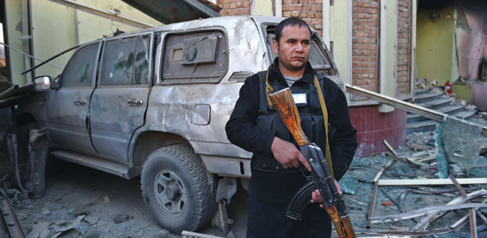 An Afghan security official stands alert among damaged buildings and a vehicle after a car bomb atta