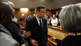 Oscar Pistorius (C) speaking with relatives as he leaves the High Court in Pretoria