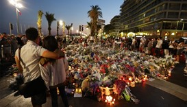 People stand in front of flowers, candles and messages laid at a makeshift memorial in Nice