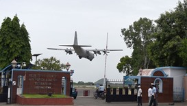 An Indian Airforce aircaft lands as Indian Airforce security personel stand guard outside Tambaram A