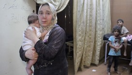 A Syrian woman carries a baby inside a makeshift hospital following strikes and shelling on the rebe