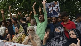 Relatives and  residents carry photographs of Pakistani national Zulfiqar Ali, who was sentenced to