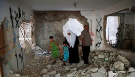 The parents of Palestinian assailant Essa Assaf inspect their family house it was partially destroye