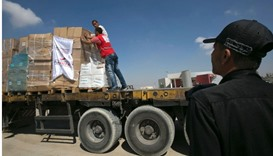 Workers stand on a truck loaded with aid parcels provided by Turkey after it entered the southern Ga