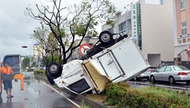 A truck sits on a traffic divider after being blown over by strong winds in the Taiwanese city of Ta