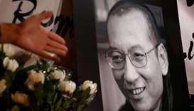Flowers are laid beside a photo the late Nobel Laureate Liu Xiaobo, outside China's Liaison Office i