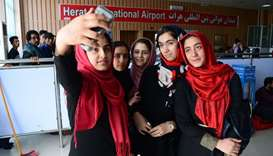 Afghan teenagers from the Afghanistan Robotic House take pictures with a mobile phone at Herat Inter