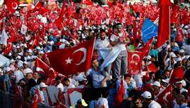 People wave Turkey's national flags as they arrive to attend a ceremony marking the first anniversar
