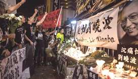 Pro-democracy activists chant slogans in front of a makeshift memorial for the late Chinese Nobel la