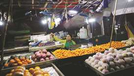 A woman sells fruit at a stall lit with battery powered lamps in Dala township, outside Yangon.