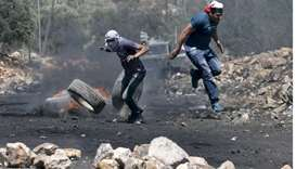 Palestinian protesters run for cover during clashes with Israeli security forces