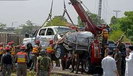 Pakistani officials use a crane to lift a security vehicle at the site of suicide bomb attack in Pes