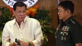 Philippine President Rodrigo Duterte (L) holds a .45 caliber handgun