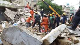 Pakistani rescue workers search for victims as they remove debris after a three story building colla