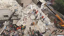 Rescue workers go through the rubble of a three-storey residential building, which collapsed early m