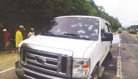 People stand next to the bullet-riddled vehicle in which some members of the Presidential Security G