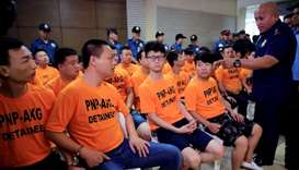 Philippine National Police (PNP) Chief Ronald Dela Rosa (R) confronts some of the 43 arrested foreig