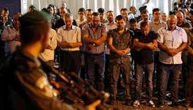 Israeli security forces stand guard in front of Palestinian Muslim worshippers praying outside Lions