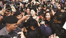 Ousted former Thai prime minister Yingluck Shinawatra greets her supporters as she leaves the Suprem