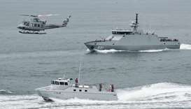 Indonesia navy soldiers on warship and helicopter are seen during the launch of coordinated patrols