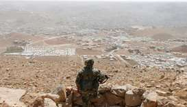 A Lebanese soldier carries his weapon as he stands at an army post in the hills above the Lebanese t
