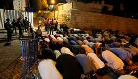 Israeli border police stand guard as Palestinians take part in evening prayers outside the Lion's Ga