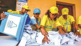 Election officials open a ballot box during counting for the parliamentary election in Dili yesterda