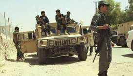 Afghan security personnel sit on atop an armoured vehicles amid an ongoing battle with Taliban milit