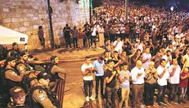 Israeli security forces stand by as Palestinian worshippers pray on Monday night outside Lions' Gate