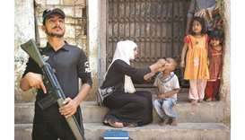 A Pakistani policeman stands guard as a health worker administers the polio vaccine to a child durin