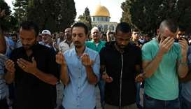 Palestinian Muslims raise their hands in prayer inside the Haram al-Sharif compound  in the old city