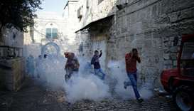 Palestinians react as a stun grenade explodes in a street at Jerusalem's Old city outside the compou