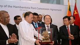 Sri Lanka's Minister Mahinda Samarasinghe (C) exchanges souvenirs with Executive VP of China Merchan