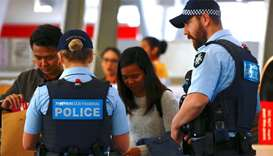 Australian Federal Police officers talk with passengers near the check-in counters at the Sydney Air
